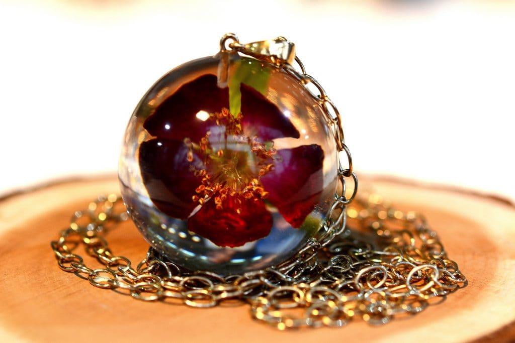 Biżuteria z żywicy. Pozłacany wisior z czerwoną różą.